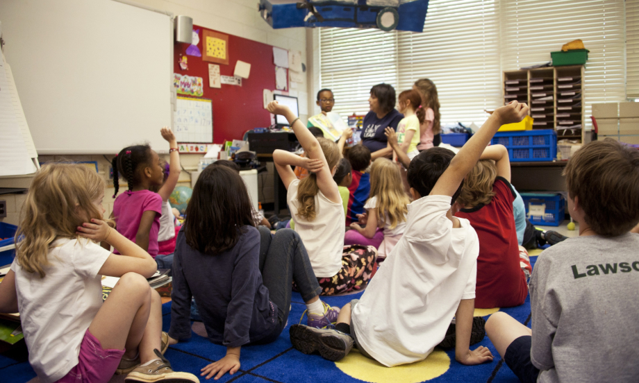 学生们正在拥挤的幼儿园教室内举手回答教师的问题。
