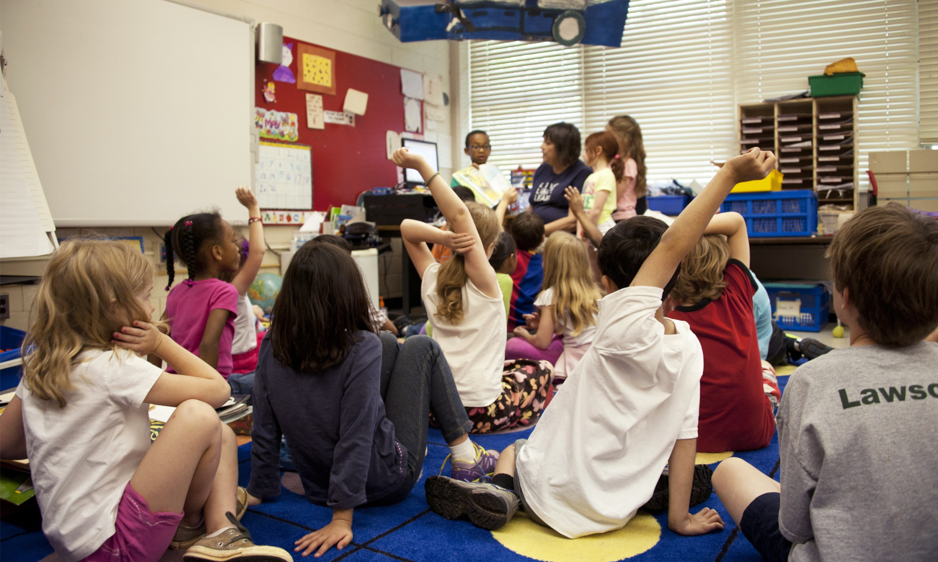 A crowded kindergarten classroom with kids raising hand to answer a teacher's question
