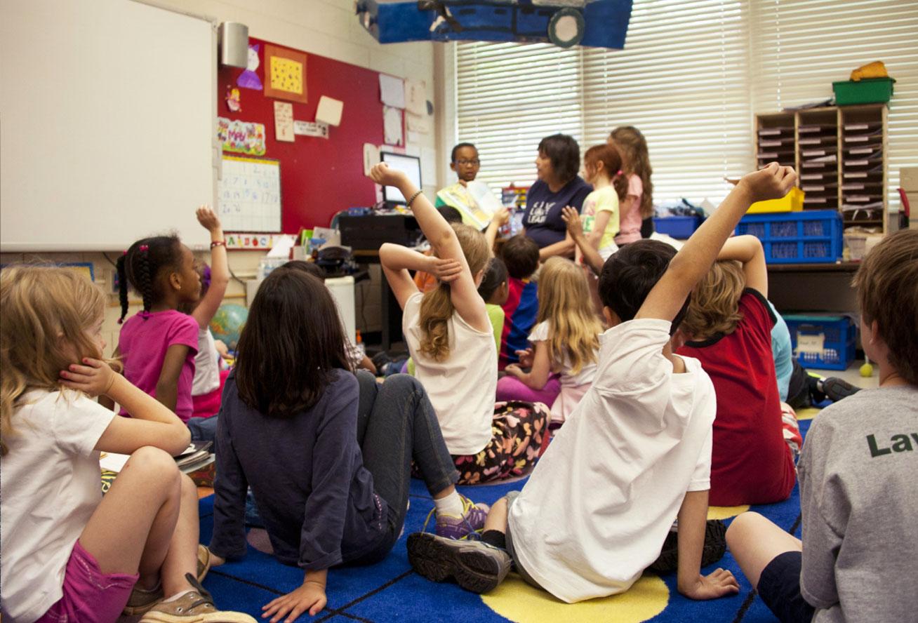 Photo of a class of children raising their hands in front of a teacher