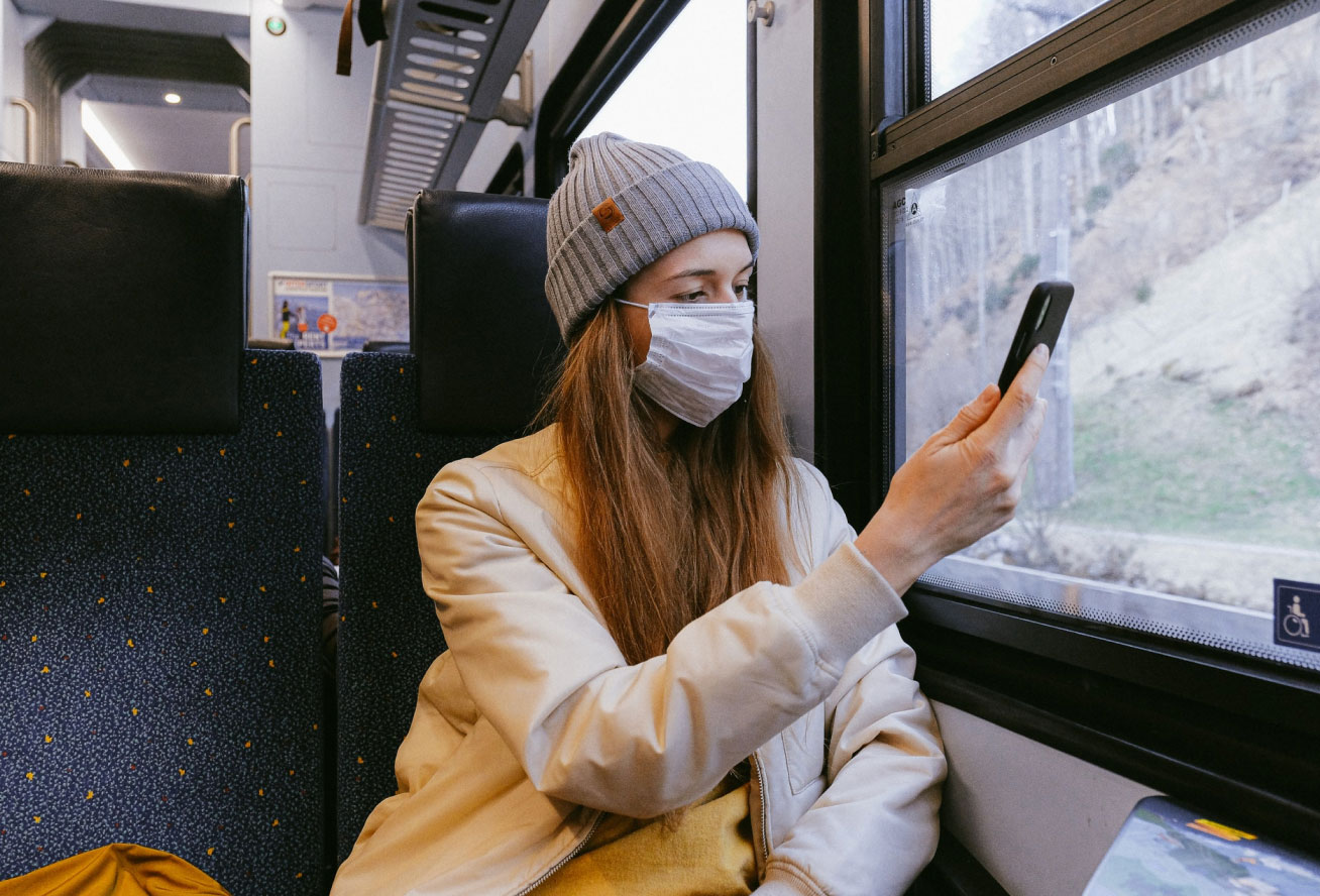 Photo of a woman on a train looking at her phone