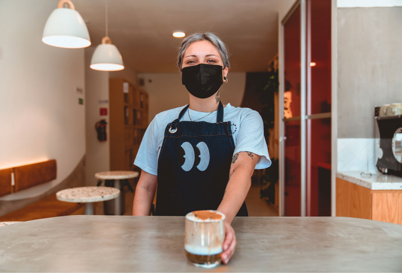 Photo of a barista serving a coffee to go