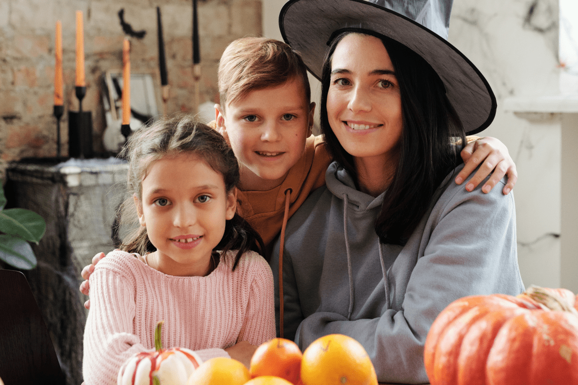 Mother wearing a witch hat with two children at a table decorating for Halloween